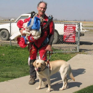 John in his flight suit holding his parachute with guide dog, Tia, by his side