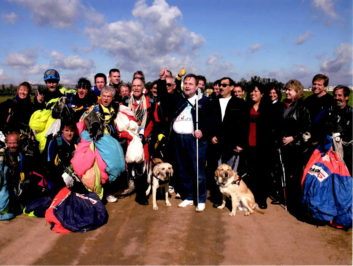 Group photo with John Fleming, Dan Rossi, their guide dogs and friends